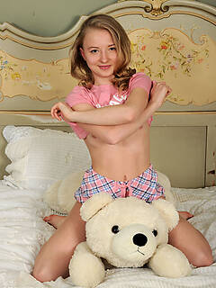 This cute and sexy teen model loves playing with her stuffed animal while stripping and posing naked.